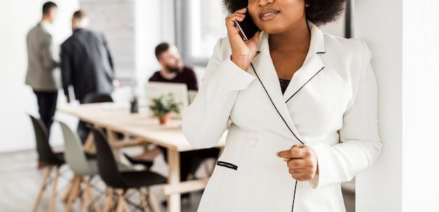Vista frontale della donna che parla al telefono Foto Gratuite
