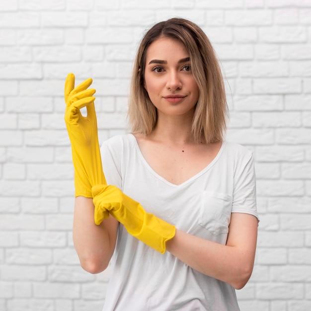 Vista frontale della donna che prepara pulire indossando i guanti Foto Gratuite