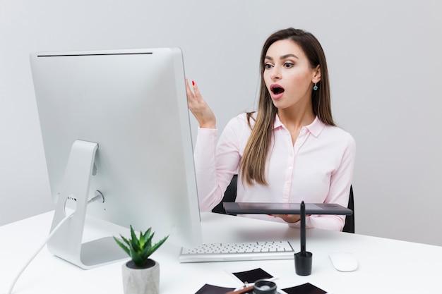 Vista frontale della donna che sembra sorpresa allo schermo di computer Foto Gratuite