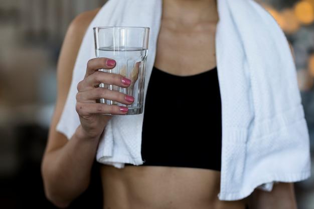 Vista frontale della donna che tiene bicchiere d'acqua Foto Gratuite