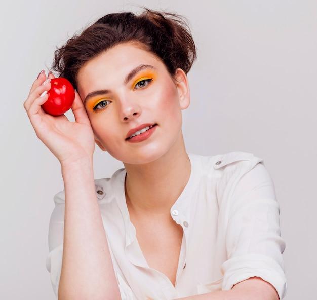 Vista frontale della donna che tiene una mela Foto Gratuite