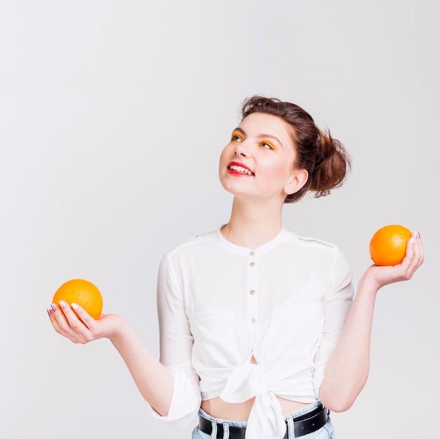 Vista frontale della donna con arance Foto Gratuite