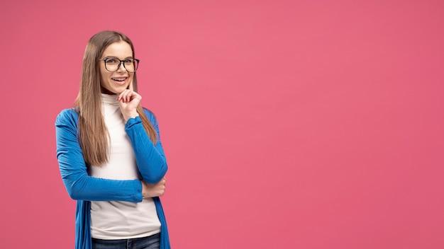 Vista frontale della donna con gli occhiali in posa come se stesse pensando Foto Gratuite