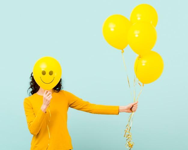 Vista frontale della donna con palloncini Foto Gratuite