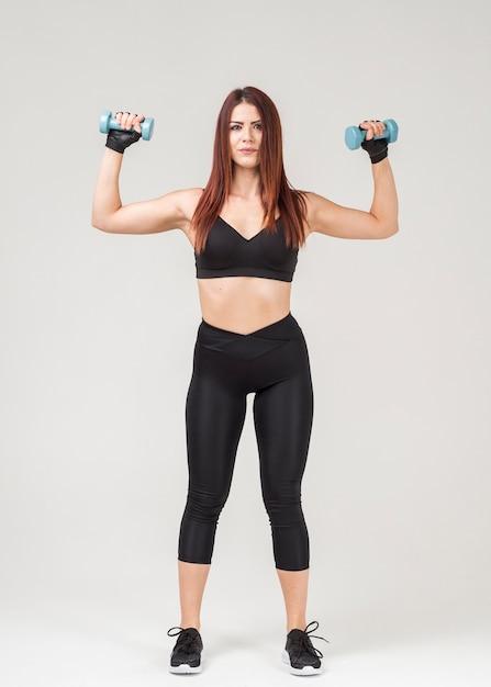 Vista frontale della donna in abbigliamento palestra che si esercita con i pesi Foto Gratuite