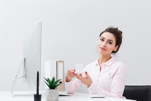Vista frontale della donna lavoratrice che tiene tazza di caffè allo scrittorio Foto Gratuite