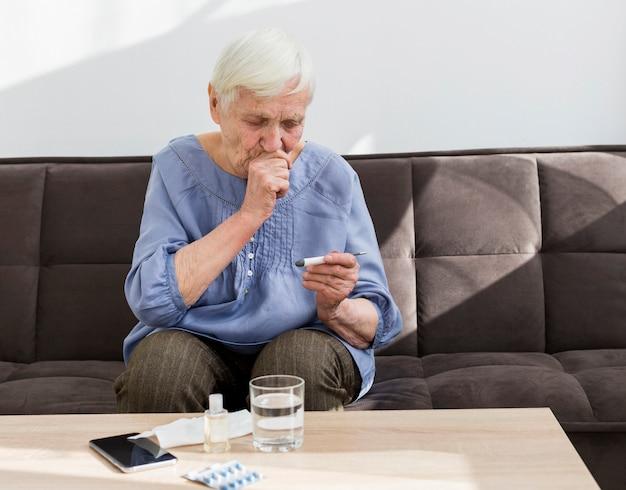 Vista frontale della donna più anziana che esamina termometro Foto Gratuite