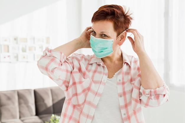 Vista frontale della donna più anziana che prova sulla mascherina medica Foto Gratuite