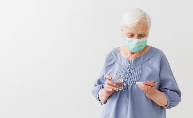 Vista frontale della donna più anziana con il termometro medico della tenuta della maschera con lo spazio della copia Foto Gratuite