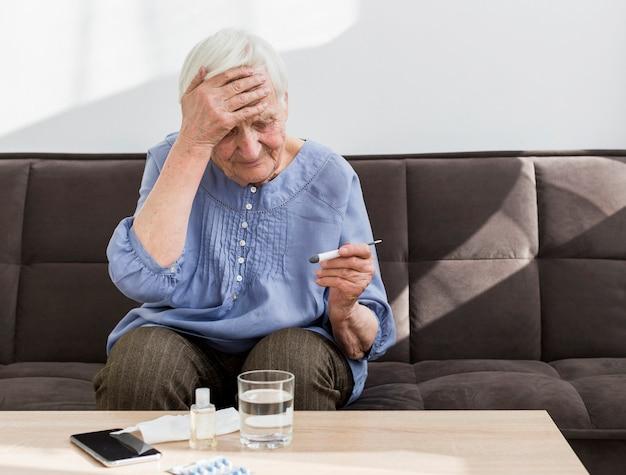Vista frontale della donna più anziana preoccupata per la temperatura sul termometro Foto Gratuite