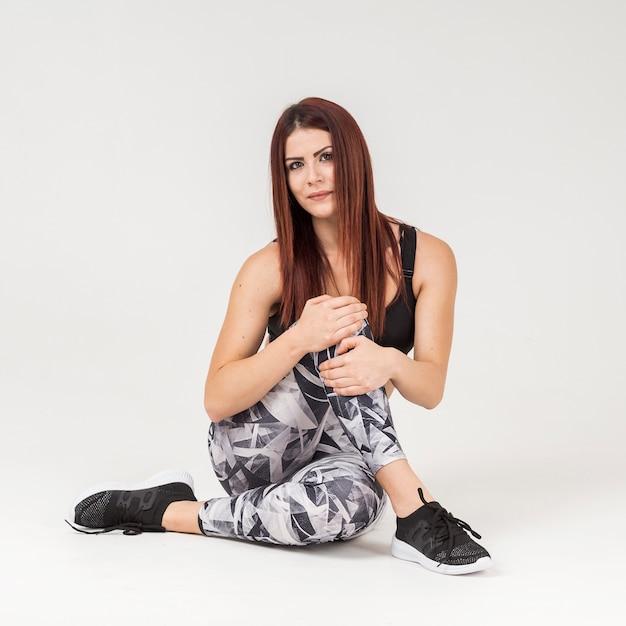 Vista frontale della donna sportiva che posa mentre indossando l'abbigliamento di allenamento Foto Gratuite