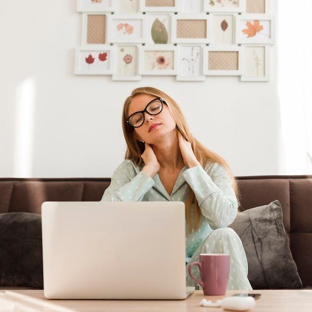 Vista frontale della donna stanca in pigiama che lavora dalla casa Foto Gratuite
