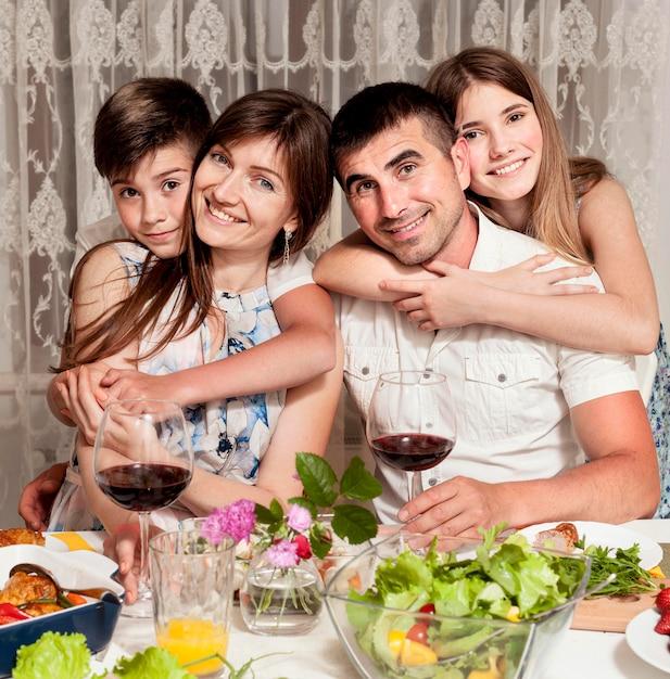 Vista frontale della famiglia felice a tavola con vino Foto Gratuite