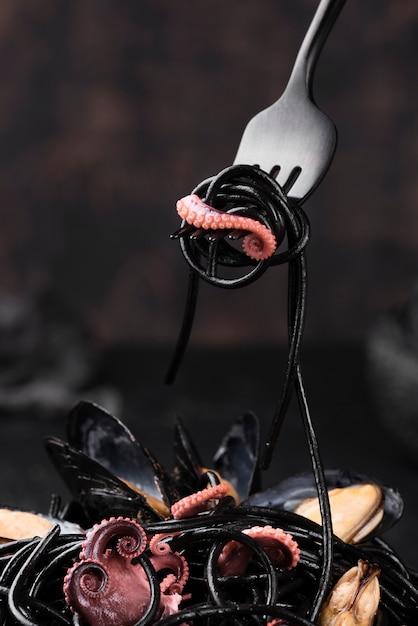 Vista frontale della forcella con pasta nera e calamari Foto Gratuite