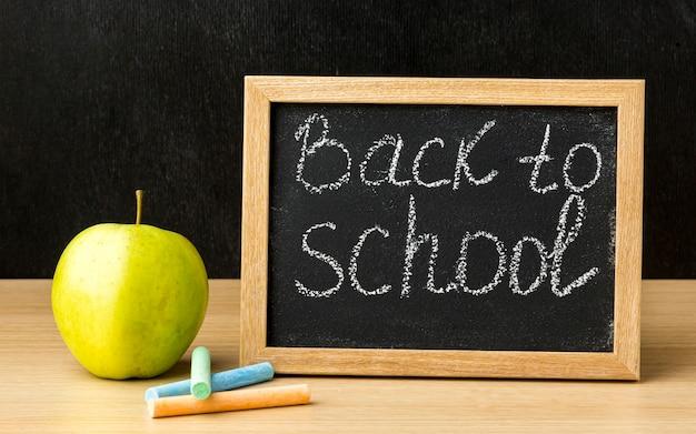 Vista frontale della lavagna con la mela per di nuovo a scuola Foto Gratuite