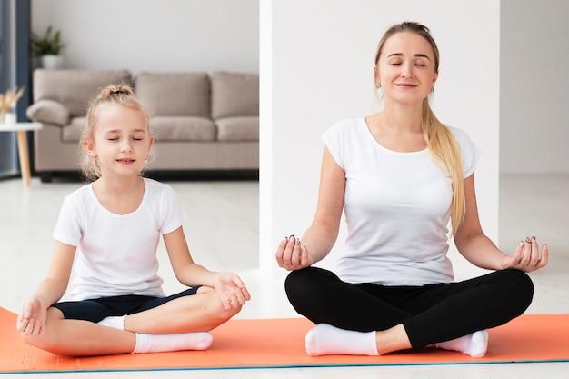 Vista frontale della madre che fa yoga con la figlia a casa Foto Gratuite