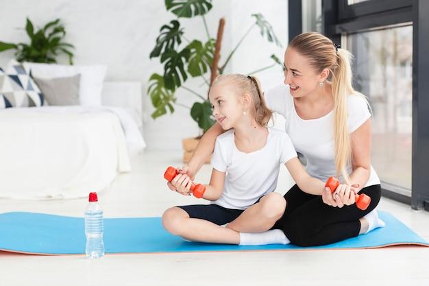 Vista frontale della madre e della figlia che si esercitano con i pesi a casa Foto Gratuite
