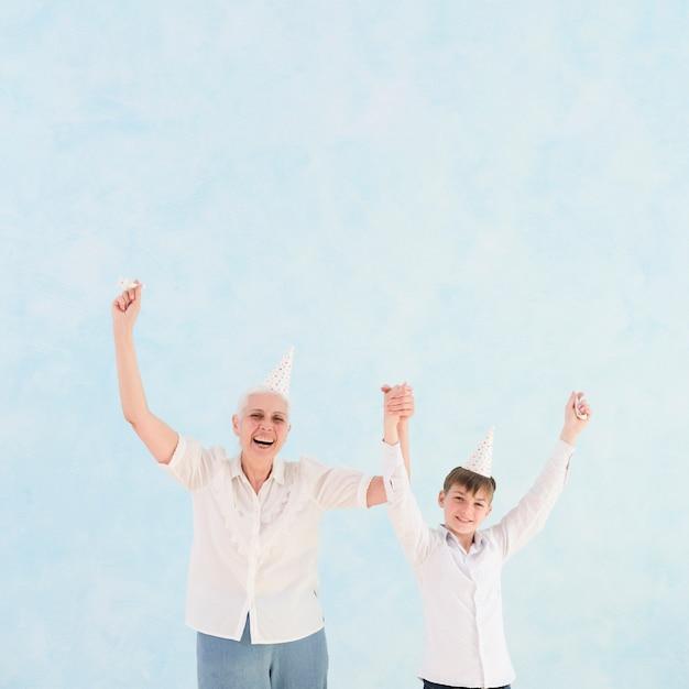 Vista frontale della nonna e del nipote felici con il braccio alzato Foto Gratuite
