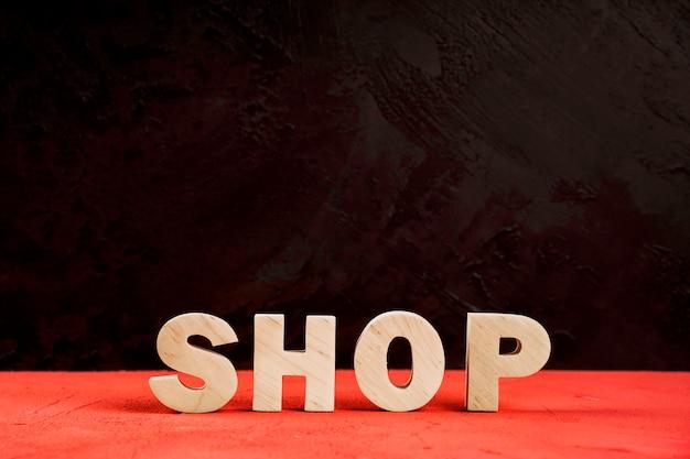Vista frontale della parola del negozio sulla tavola rossa Foto Gratuite