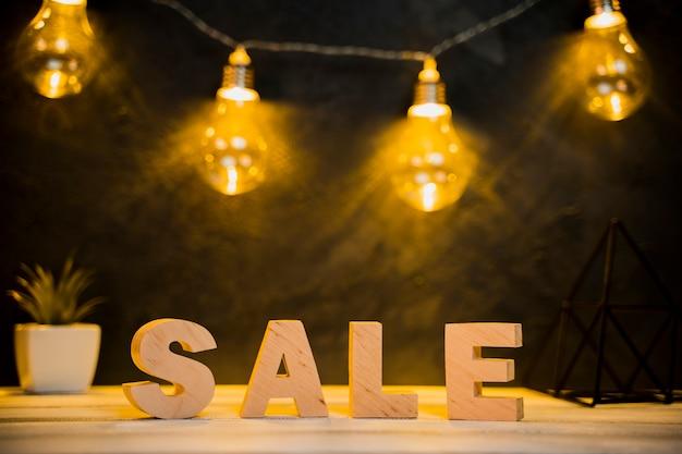 Vista frontale della parola di vendita e lampadine con tavolo in legno Foto Gratuite