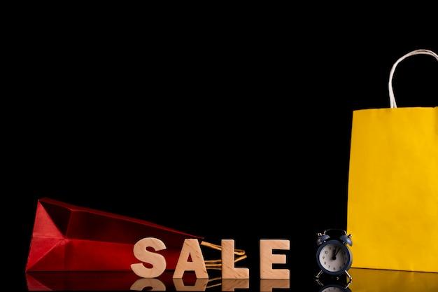 Vista frontale della parola e della borsa di vendita con fondo nero Foto Gratuite