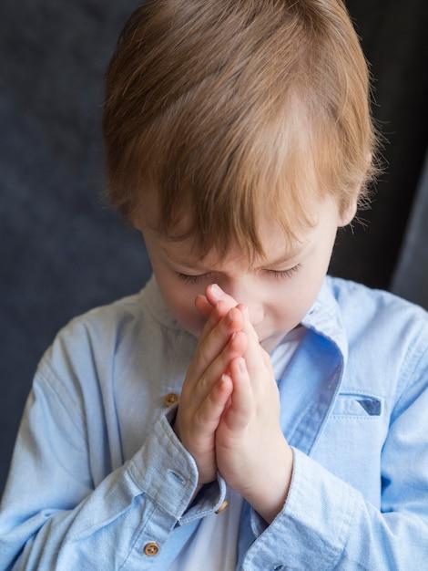 Vista frontale della preghiera del ragazzino Foto Gratuite