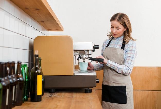 Vista frontale della ragazza di barista che produce caffè Foto Gratuite