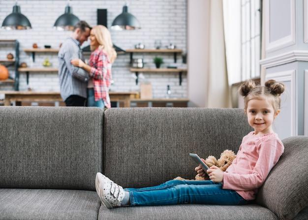 Vista frontale della ragazza sorridente che tiene compressa digitale con i suoi genitori vaghi nella priorità bassa Foto Gratuite