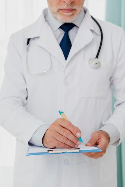 Vista frontale della scrittura del medico negli appunti Foto Gratuite