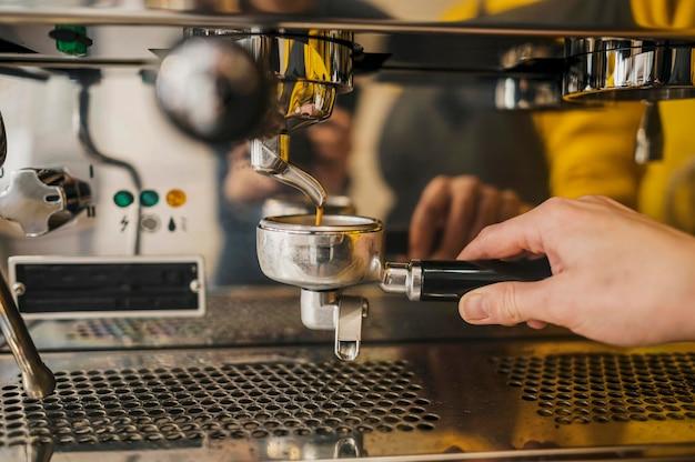 Vista frontale della tazza della macchina da caffè tenuta dal barista Foto Gratuite
