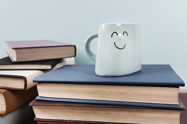 Vista frontale della tazza felice sui libri con sfondo semplice Foto Gratuite