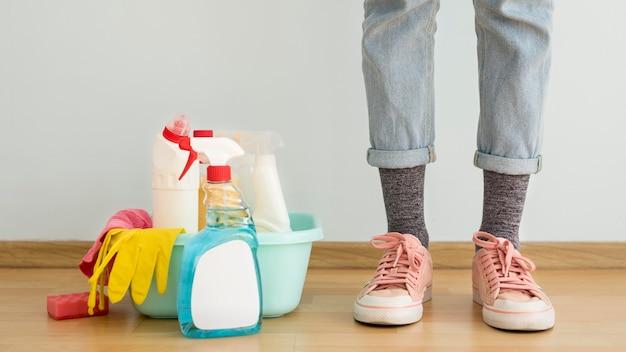 Vista frontale delle gambe con soluzioni detergenti e guanto Foto Gratuite