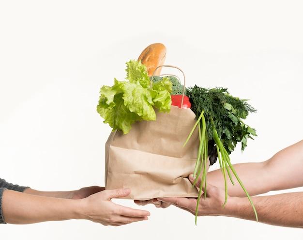 Vista frontale delle paia delle mani che tengono la borsa di drogheria Foto Gratuite