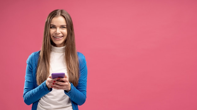 Vista frontale dello smartphone della tenuta della donna di smiley Foto Gratuite