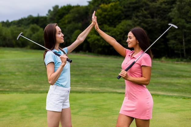Vista frontale di alto fiving dei giovani golfisti Foto Gratuite