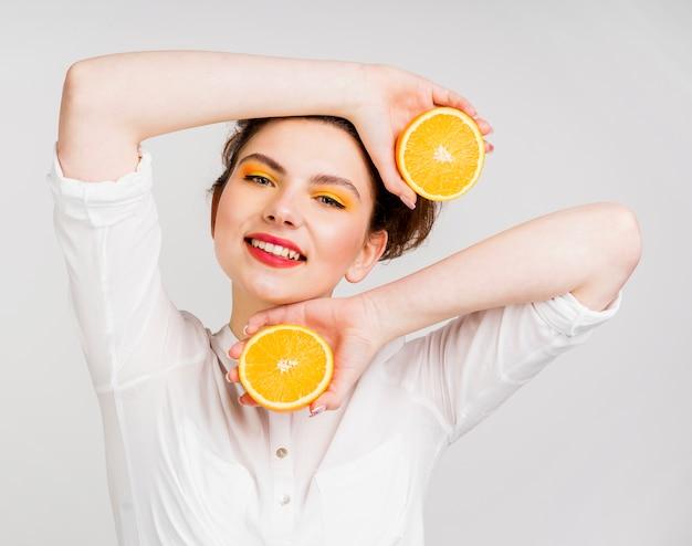 Vista frontale di bella donna con l'arancia Foto Gratuite