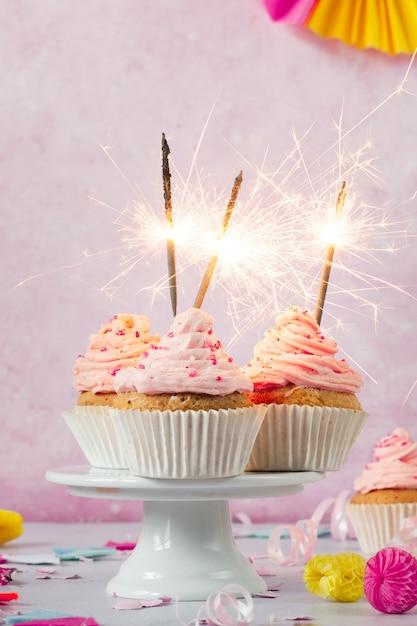 Vista frontale di cupcakes di compleanno con glassa e stelle filanti Foto Gratuite
