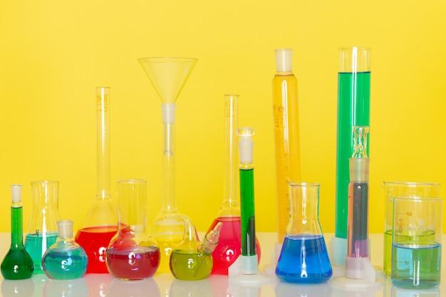 Vista frontale di diverse soluzioni colorate all'interno delle boccette sul tavolo Foto Gratuite
