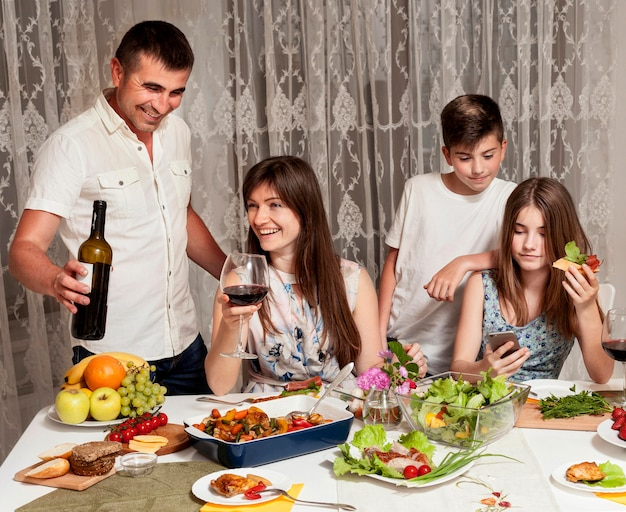 Vista frontale di genitori e figli felici a tavola Foto Gratuite