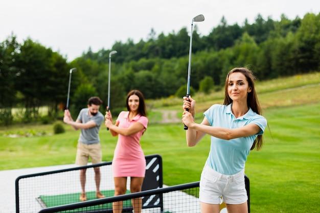 Vista frontale di giovani giocatori di golf con stick up Foto Gratuite
