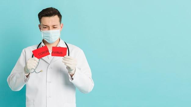 Vista frontale di medico che ostacola carta lacerata con lo spazio della copia e del coronavirus Foto Gratuite