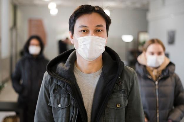 Vista frontale di persone con maschere mediche Foto Gratuite