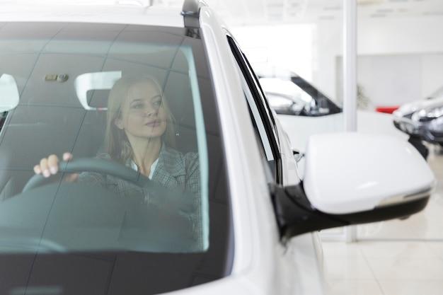 Vista frontale di una donna bionda in macchina Foto Gratuite