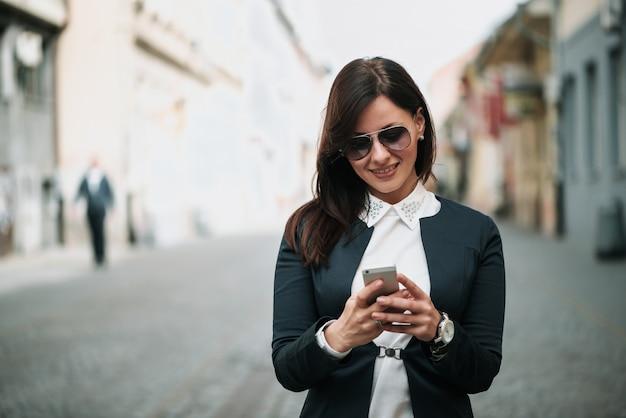 Vista frontale di una donna felice moda camminando e utilizzando uno smart phone in una strada cittadina Foto Premium