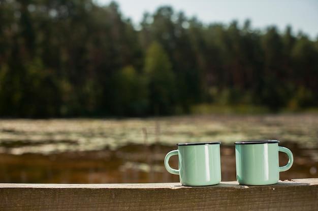Vista frontale due tazze sul ponte di legno Foto Gratuite