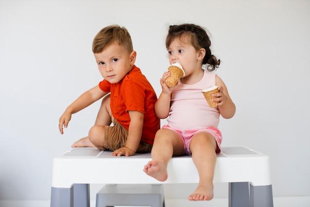 Vista frontale fratelli con gelato Foto Gratuite