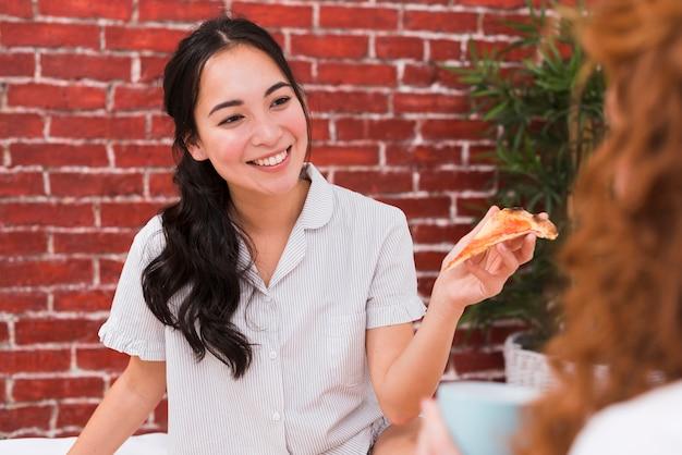 Vista frontale giovani amici che condividono la pizza Foto Gratuite