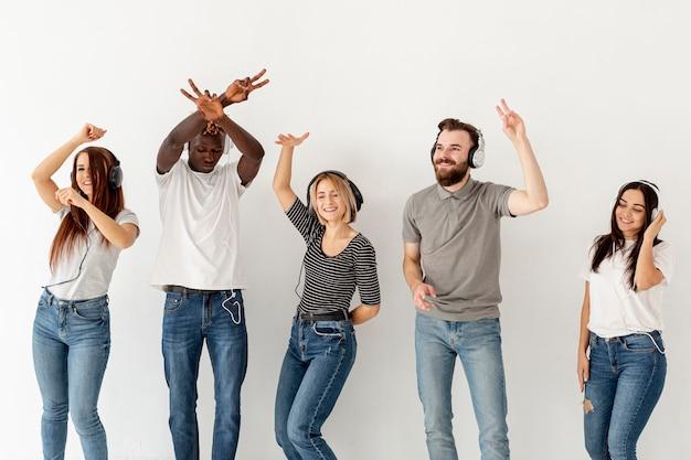 Vista frontale giovani amici con le cuffie che ballano Foto Gratuite