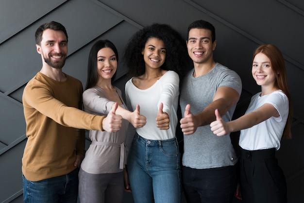 Vista frontale gruppo di giovani con pollice in alto Foto Gratuite