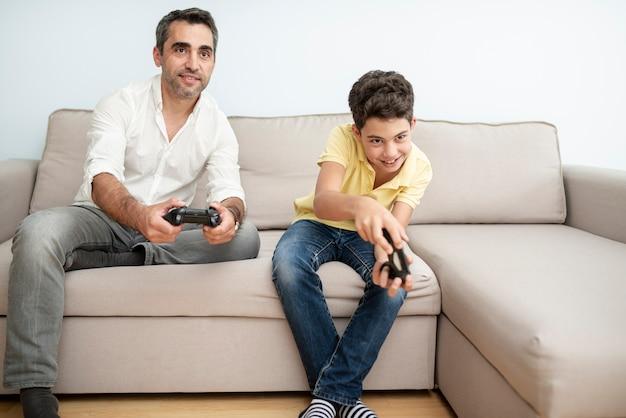 Vista frontale padre e figlio che giocano con i controller Foto Gratuite